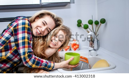 Beautiful young woman with a child of five years at the kitchen near the sink laugh and smile together - stock photo