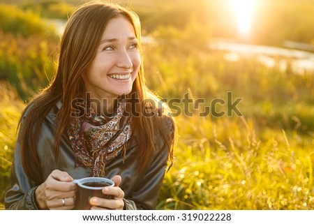 Beautiful young woman with a cup of tea outdoor