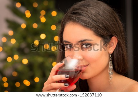 Beautiful young woman with a glass of champagne wishes you a holiday - stock photo