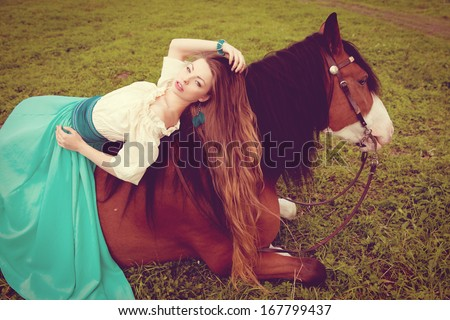 Beautiful young woman with a horse in the field. Girl on a farm with animal. Luxury woman outdoors