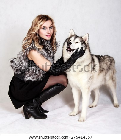 Beautiful young woman with a husky dog over grey background