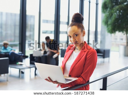 Beautiful young woman with a laptop in office. African american woman standing by a railing with colleagues sitting in background. - stock photo