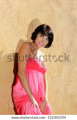 beautiful young woman with a long  pink dress posing on the wall - stock photo