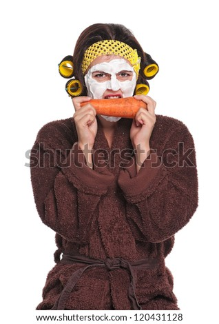 Beautiful young woman with a mask on her face eats carrot isolated over white - stock photo
