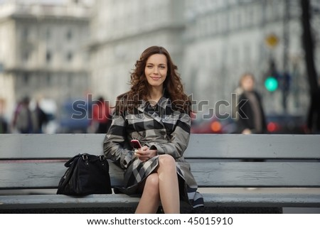 beautiful young woman with a mobile phone with city life on background