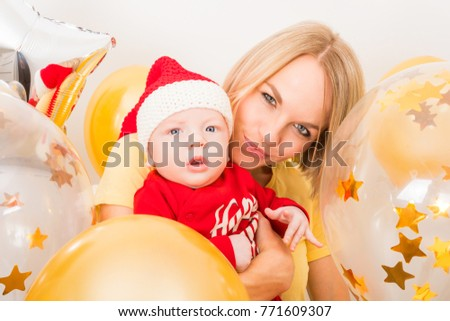 Beautiful young woman with a newborn child in red Christmas costume and Santa Claus hat on a background of gold and transparent balloons with a confit inside. New Year