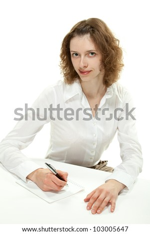 Beautiful young woman with a pen and sheet of paper sitting at the table; concept of consumer service