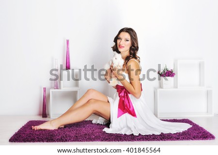 Beautiful young woman with a pet rabbit in studio