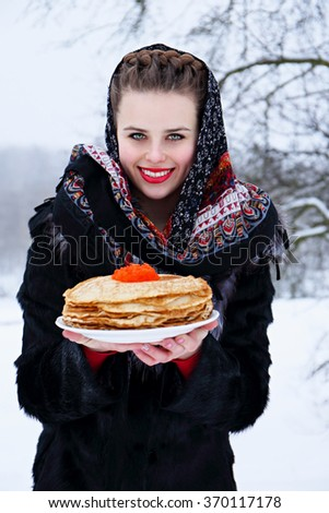 Beautiful young woman with a plate of pancakes and red caviar