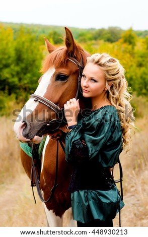 Beautiful young woman with a red horse outdoor. The end of summer and beginning of autumn. Beautiful and colorful landscape. Blonde Girl riding the stallion in the field. The concept . Hippotherapy