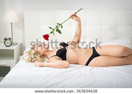 Beautiful young woman with a rose on the bed - stock photo