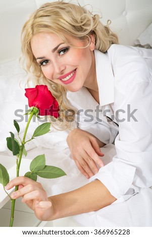 Beautiful young woman with a rose on the bed