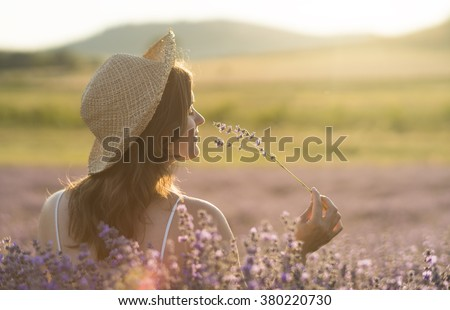 Beautiful young woman with a straw hat holding a bunch of lavender flowers and enjoying their fragrance in the middle of a lanvender field in the light of the setting sun. - stock photo