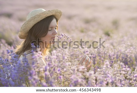 Beautiful young woman with a straw hat holding a bunch of lavender flowers and enjoying their fragrance in the middle of a lavender field in the light of the setting sun. - stock photo