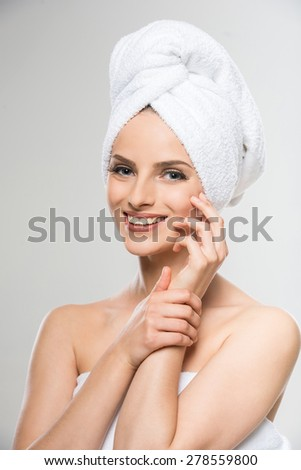 Beautiful young woman with a towel on her head after bath. - stock photo
