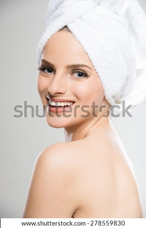 Beautiful young woman with a towel on her head after bath. Grey background. - stock photo