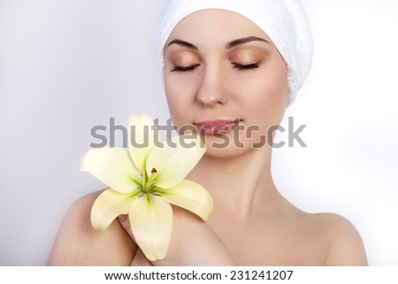 beautiful young woman with a towel on her head after bath holding flower