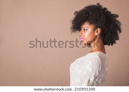 Beautiful young woman with afro in studio - stock photo