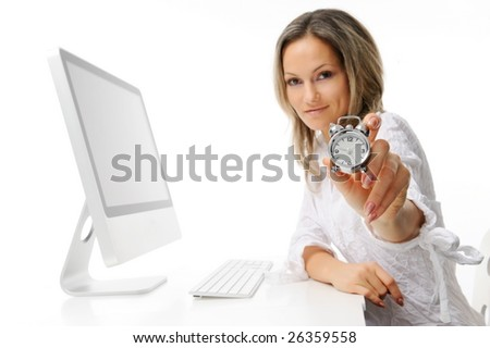 beautiful young woman with alarm clock in front of the computer - stock photo