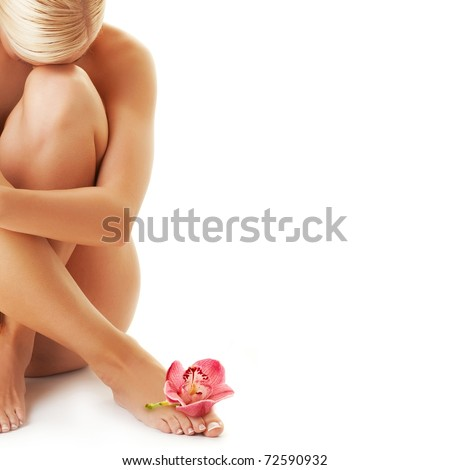 Beautiful young woman with an orchid on her leg - stock photo
