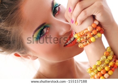 Beautiful young woman with artistic makeup in studio - stock photo