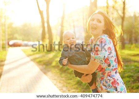 Beautiful young woman with baby boy kid boy standing on the meadow on the summer sunset. Happy family in the park. Outdoors. Mother with children.