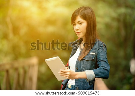 beautiful young woman with backpack and tablet Standing on the bridge,adventure, travel, tourism, hike and people concept