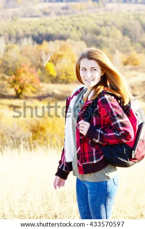 Beautiful young woman with backpack outdoors