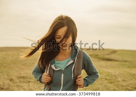 Beautiful young woman with backpack walking on meadow. Portrait of hiker girl outdoor