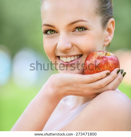 Beautiful young woman with bare shoulders points at apple and smiles, against green of summer park. - stock photo