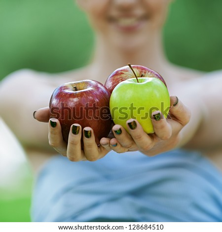 Beautiful young woman with bare shoulders stretches apple, against green of summer park. - stock photo