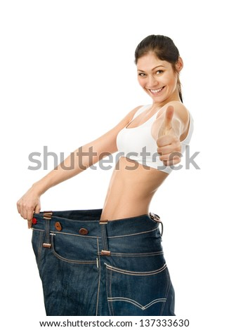 beautiful young woman with big jeans. looking at camera. isolated on white background - stock photo