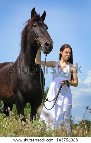 Beautiful young woman with black horse