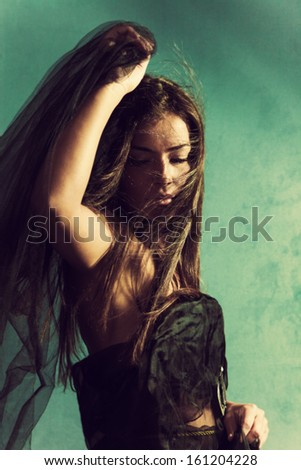 beautiful young woman with black veil in one hand, hair flying across her face, eyes closed, green wall behind her