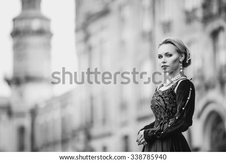 Beautiful young woman with blond hair in a black dress cut medieval historical walks around the old castle, the magic atmosphere of magic and fairy tales