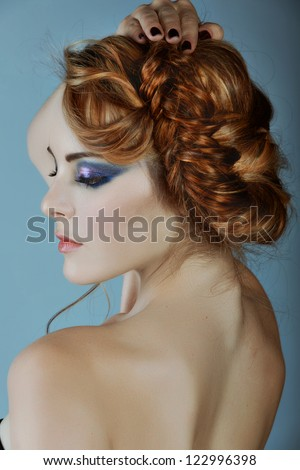beautiful young woman with blond red hair in braids and dramatic eye makeup - stock photo