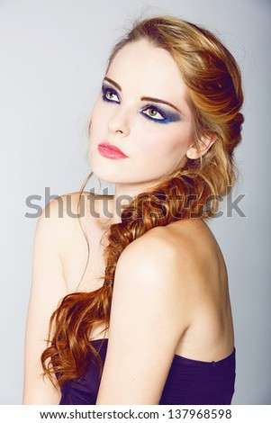 beautiful young woman with blond red hair in fishtail braid and dramatic eye makeup  - stock photo