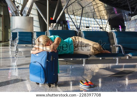 beautiful young woman with blond short hair with a suitcase sleep on a chair at the airport and waiting for her flight - stock photo