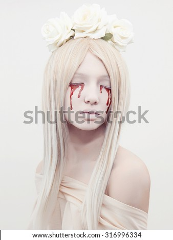 beautiful young woman with blood from her eyes.blond sexy halloween girl.horror with flowers - stock photo