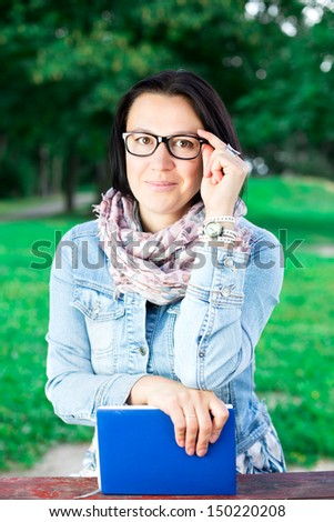 Beautiful young woman with book in park - stock photo