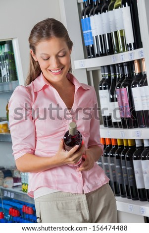 Beautiful young woman with bottle of alcohol at supermarket - stock photo