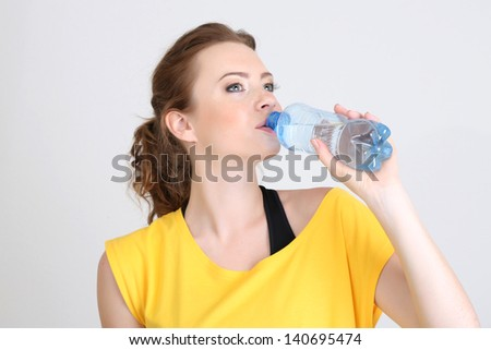 Beautiful young woman with bottle of water - stock photo