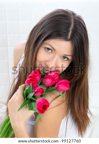 Beautiful young woman with bouquet of red tulips flowers sitting on couch, smiling