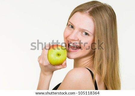 Beautiful young woman with brackets on teeth eating apple on white background - stock photo