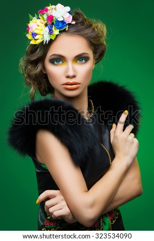 Beautiful young woman with bright colorful makeup and flowers on head in fur vest coat - stock photo