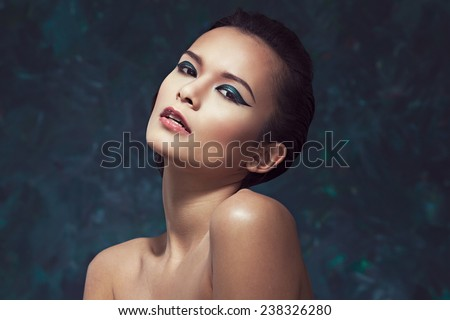 Beautiful young woman with bright creative makeup - stock photo