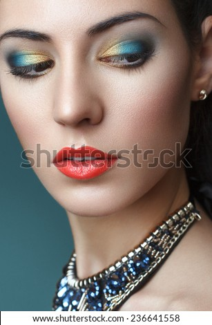 beautiful young woman with bright make up on blue background. Party look - stock photo