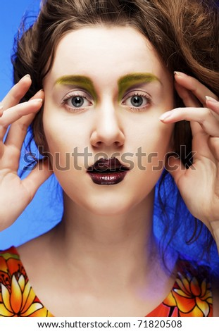 beautiful young woman with bright make-up over blue background