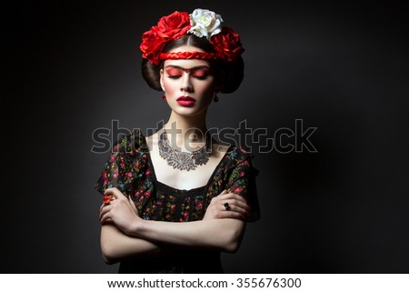 Beautiful young woman with bright red make up and roses on head. Over black background. Copy space. - stock photo