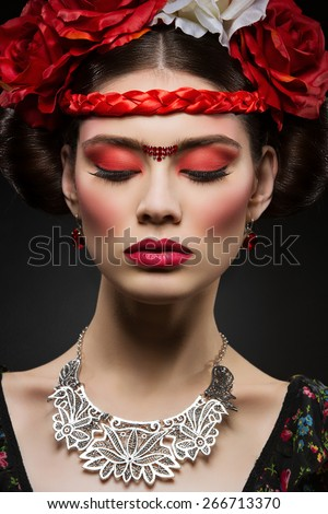 Beautiful young woman with bright red make up looking like Frida Kahlo. Over black background